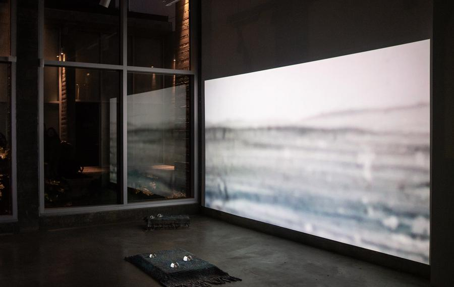 Installation view of large video projection that extends as a reflection in a window